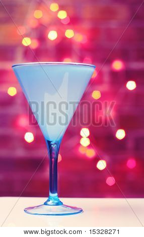 Turquoise martini glass, brick wall and fairy lights in the background