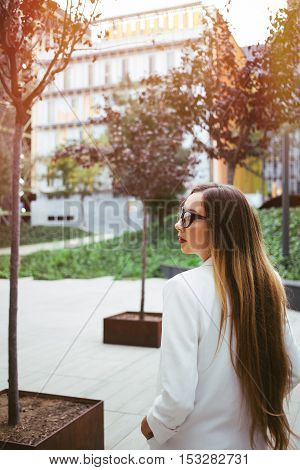 Attractive Caucasian young woman with long hair is wearing stylish glasses and white suite and  walking on the background of urban buildings. Business people concepts. Urban architecture area