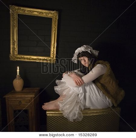 Woman wearing vintage clothing and mop,sitting on a gold chest, vintage ornate frame on a brick wall, candle light