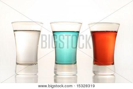 Tres vasos de chupito con rojo, azul y ver a través de líquido