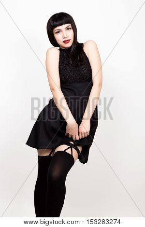 beautiful young woman in a short black dress and black stockings.