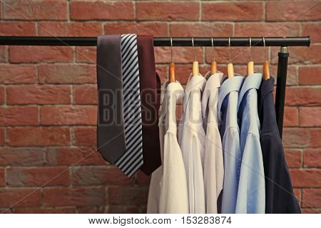 Hangers with male shirts and ties on clothes rail against brick wall background