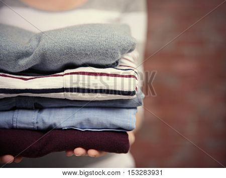 Woman holding pile of clothes, closeup