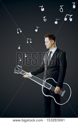 Side view of young businessperson in suit playing abstract drawn guitar on dark grey background. Music concept