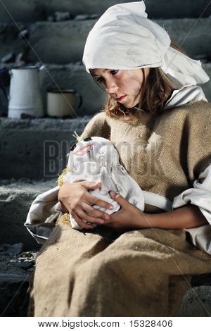 Sad poor girl wearing dirty vintage clothes, holding a smiling doll