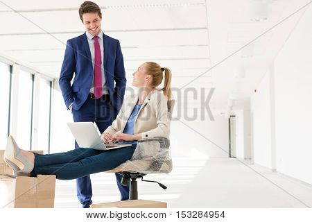 Young businessman talking with female colleague using laptop in new office