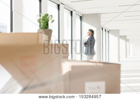 Distant image of businessman looking through window with cardboard boxes in foreground