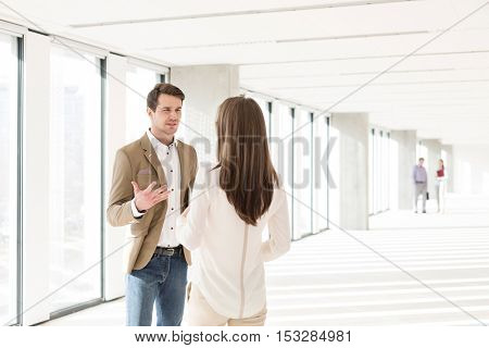 Young businessman discussing with female colleague in new office