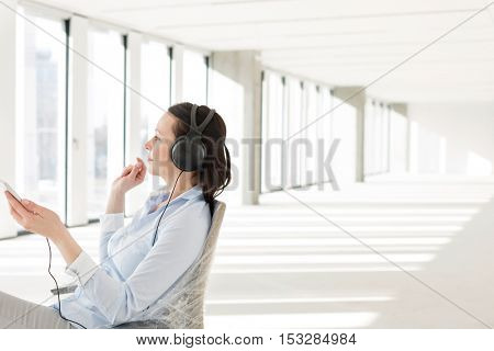 Side view of mid adult businesswoman listening music through headphones in empty office