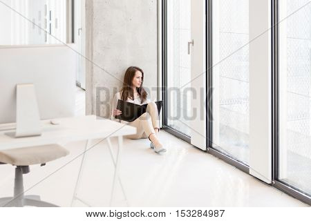 Young businesswoman holding file while sitting on floor in new office