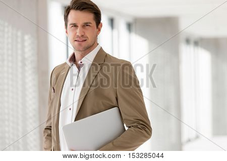 Portrait of young businessman holding laptop in new office
