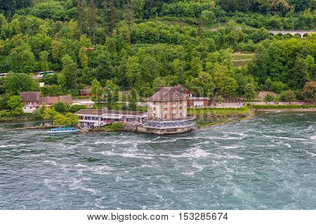 Neuhausen am Rheinfall Switzerland - May 24 2016: Rhine River at Rhine Falls and Castle Woerth in the Neuhausen am Rheinfall in the Canton of Schaffhausen Switzerland. Famous waterfall in Europe. Swiss travel destination and tourist attraction.