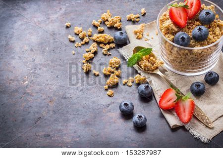 Breakfast, healthy food concept. Homemade muesli granola with berries in a glass on rusty black table. Selective focus, copy space background