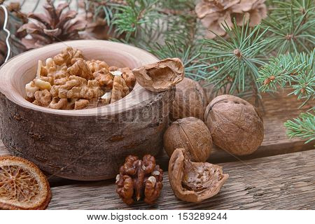 Composition of bowl with walnuts and natural decor on wooden background, close up view