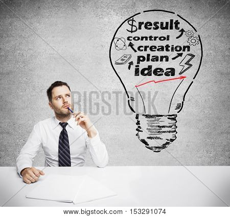 Thoughtful businessman at workplace with creative light bulb on concrete wall background. Business idea concept
