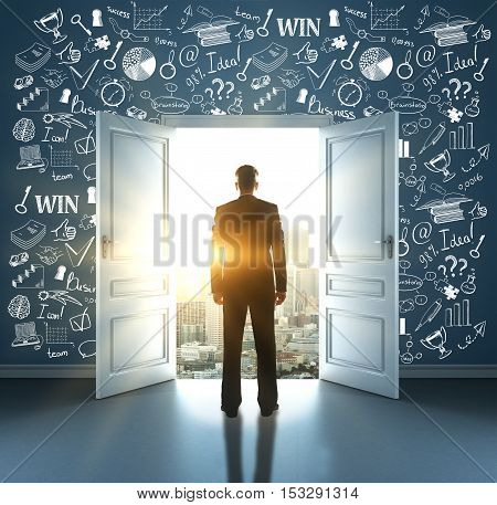 Back view of young businessman standing in room with business icons on wall against open door with city view and sunlight. Success concept