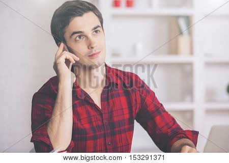 Portrait of attractive young guy in casual red shirt talking on cellular phone