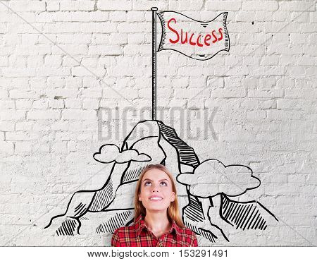 Smiling young woman on brick background with creative mountain peak sketch. Success and leadership concept