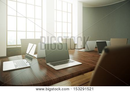 Close up of blank laptop on wooden conference table in room with concrete walls and windows. Mock up 3D Rendering