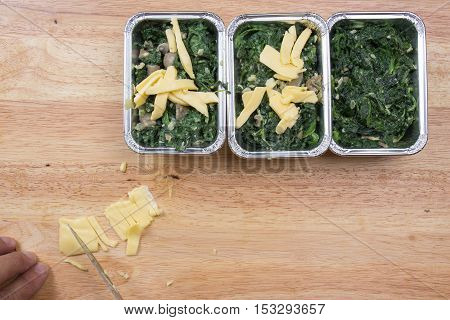 Slicing cheese to spinach box / cooking Baked spinach concept