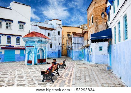 CHEFCHAOUEN, MOROCCO - JANUARY 2, 2014: Children resting at square of Chefchaouen Medina.