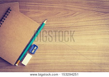 top view of wooden work desk with notebook pencil and eraser - blank space for your content