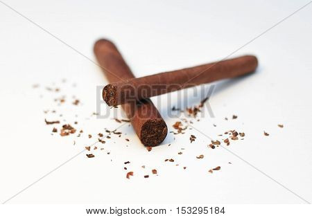 one cigar on top of another on white background