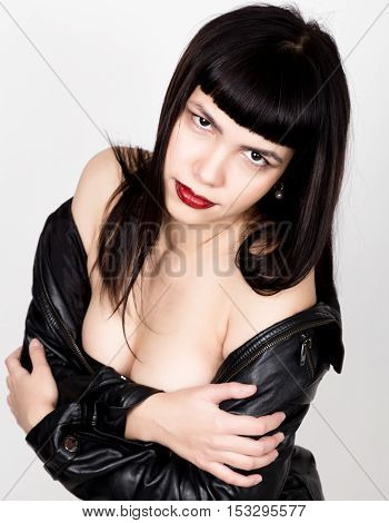 Portrait of beautiful young woman in a leather jacket, standing turned with bare shoulders. posing at camera.