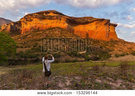 Tourist Holding Smart Phone And Taking Photo At Scenic Cliff Illuminated By Sunset Light In The Maje