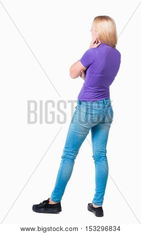 back view of standing young beautiful  woman.  girl  watching. Rear view people collection.  backside view of person.  Long-haired blonde in the purple shirt looks pensively to the side.