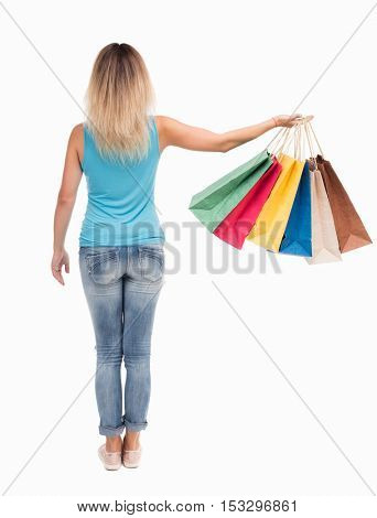 back view of woman with shopping bags . beautiful girl in motion. backside view person.  girl in a blue t-shirt standing with shopping. blonde in a blue sweater holding colorful bags at arm's length