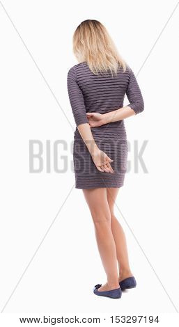 back view of standing young beautiful  woman.  girl  watching. Rear view people collection.  backside view of person.  The girl in a brown dress standing with hands clasped behind his back.