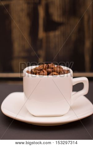 Coffee beans in a white cup on a dark wooden background
