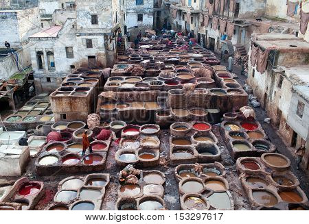 FEZ, MOROCCO - JANUARY 4, 2014: Men working hard in the tannery souk.