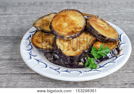Fried eggplant on a plate and gray wood background, rustic