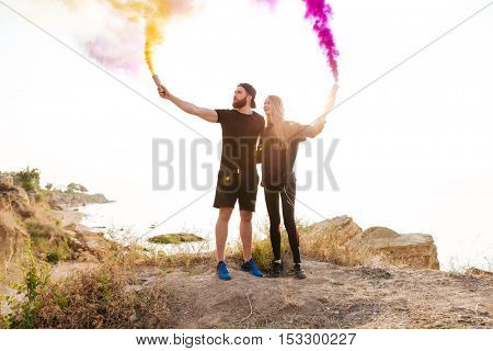 Full length portrait of a young man and woman with smoke bombs standing at the seaside