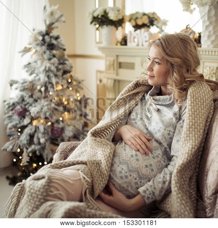 Beautiful Pregnant Woman In Comfy Clothes. Sitting In A Chair Near The Christmas Tree.