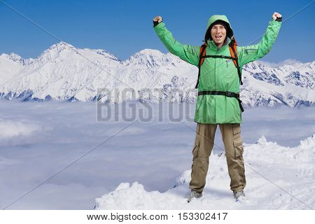 Happy male mountaineer man with raised arms. In background high mountains above clouds .