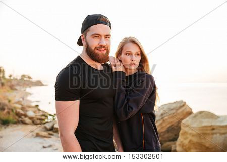 Young beautiful sports couple standing together at the seaside during sunset