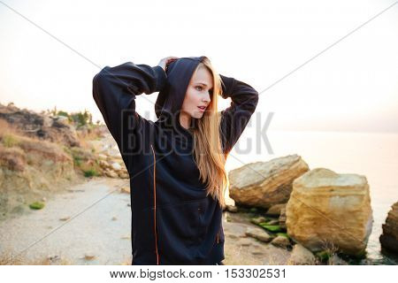 Young sports woman in sweatshirt resting after jogging training on beach at sunset