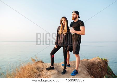 Full length portrait of an attractive sports couple standing on a hill and looking at something