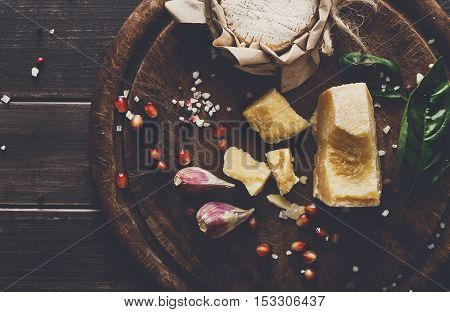 Cheese delikatessen background closeup on rustic wood. Wooden desk with parmesan, camembert and brie cuts decorated with garlic, tomato and basil, top view image with copy space