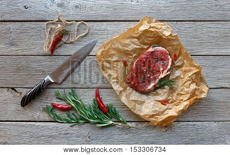 Raw beef steak in craft paper on dark wooden table background, top view. Fresh juicy meat, knife, rosemary and chili peppers. Cooking ingredients, butcher's and grocery concept