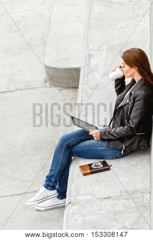 Girl sitting with a tablet in hands. Remote operation concept. Online education students. Online shopping