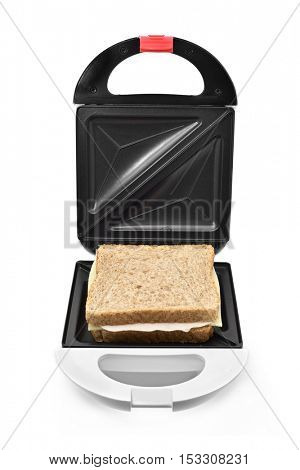 a sandwich ready to be toasted in an electrical sandwich toaster, on a white background