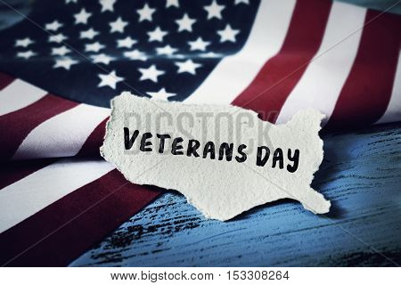 the text veterans day written in a piece of paper in the shape of the United States and the American flag on a rustic blue wooden background