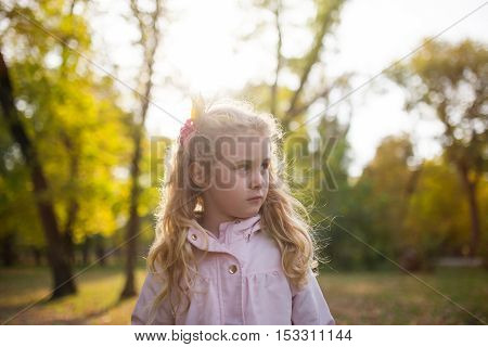 Portrait of cute blonde girl standing in autumn park
