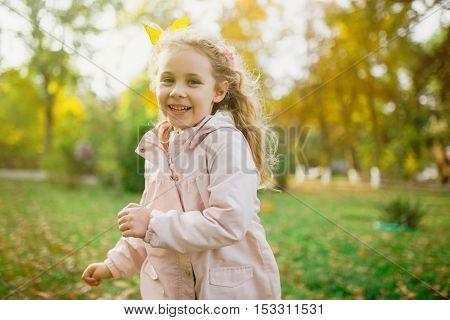Happy child girl having fun in autumn park.