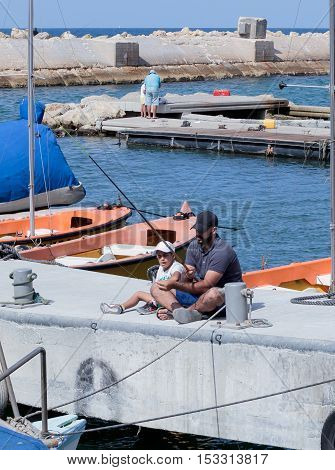 Father And Son Fishing On The Waterfront In Yafo, Israel
