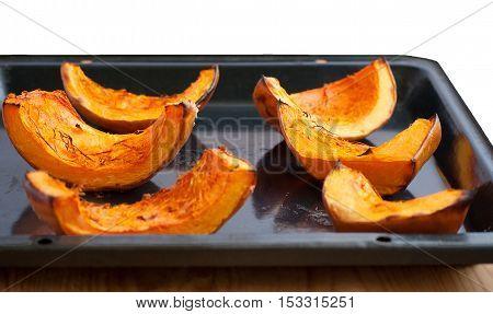 Baked pumpkin pieces on black baking sheet